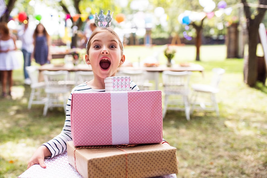 A girl holding birthday gifts at a backyard birthday party